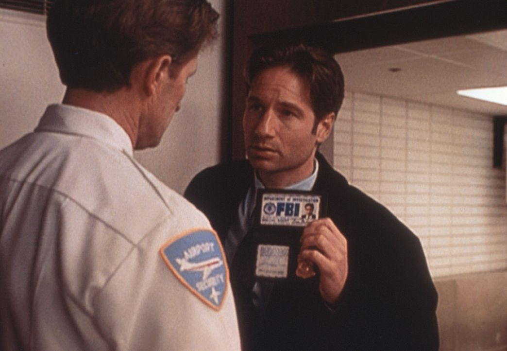 Am Flughafen wird Mulder (David Duchovny) von einem Sicherheitsbeamten überprüft ... - Bildquelle: TM +   2000 Twentieth Century Fox Film Corporation. All Rights Reserved.