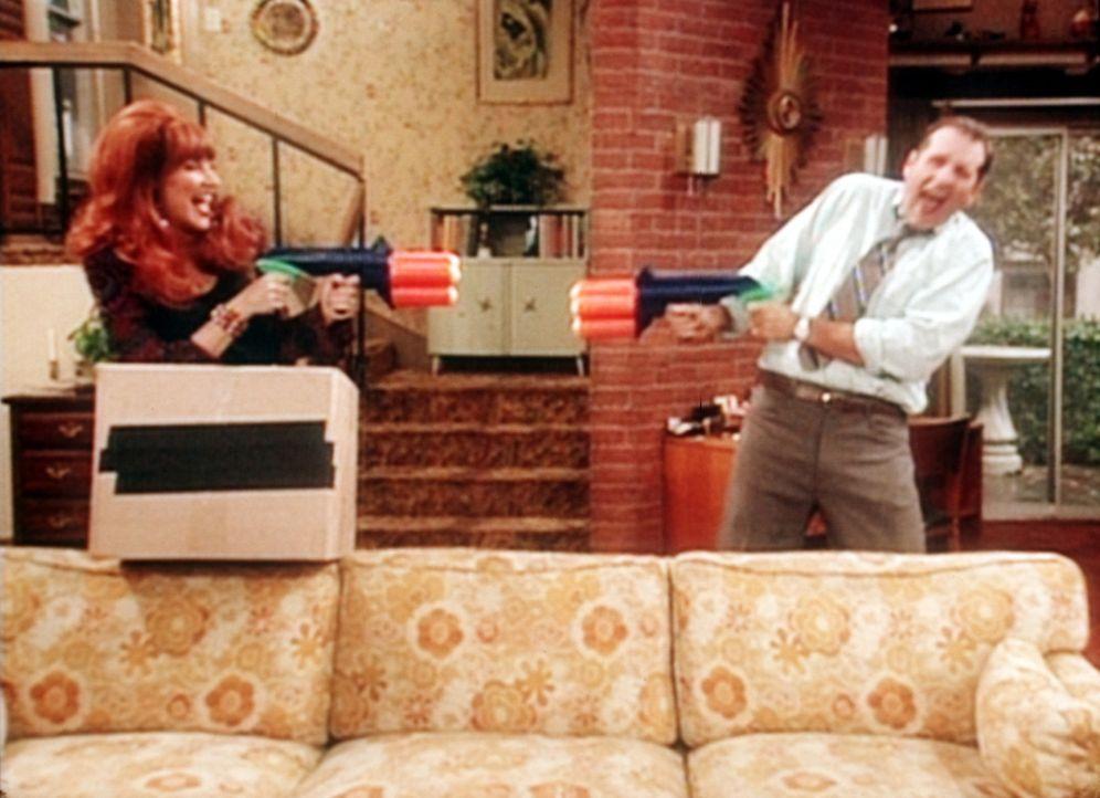 """Al Bundy (Ed O'Neill, r.) spielt begeistert mit Ehefrau Peggy (Katey Sagal, l.) mit altem Kinderspielzeug, das von einer Aktion """"Waffen gegen Spielz... - Bildquelle: Sony Pictures Television International. All Rights Reserved."""