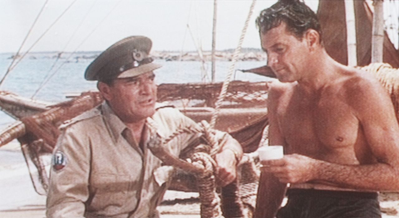 Major Warden (Jack Hawkins, l.) erzählt Shears (William Holden, r.) von seinem Plan, die Brücke am Kwai in die Luft zu sprengen ...