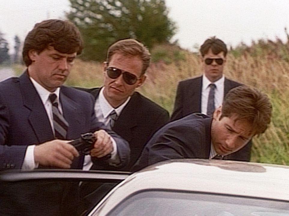 Der FBI-Agent Fox Mulder (David Duchovny, r.) wird vom militärischen Sicherheitsdienst unsanft aufgefordert, das Gelände von Ellens Airbase umgehend... - Bildquelle: TM +   2000 Twentieth Century Fox Film Corporation. All Rights Reserved.