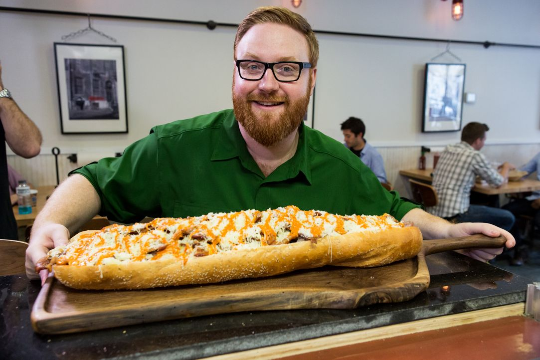 "Josh Denny ist gespannt, was das riesige Sandwich aus dem ""Jake's Sandwich Board"" zu bieten hat. Doch damit ist seine Reise durch Philadelphia noch... - Bildquelle: Ben Leuner 2016, Television Food Network, G.P. All Rights Reserved."