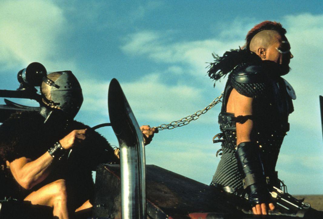 Hier erkennt man sofort, wer das Sagen hat: Anführer Humungus (Kjell Nilsson, l.) lässt sich von Wez (Vernon G. Wells, r.) kutschieren ... - Bildquelle: Warner Bros.