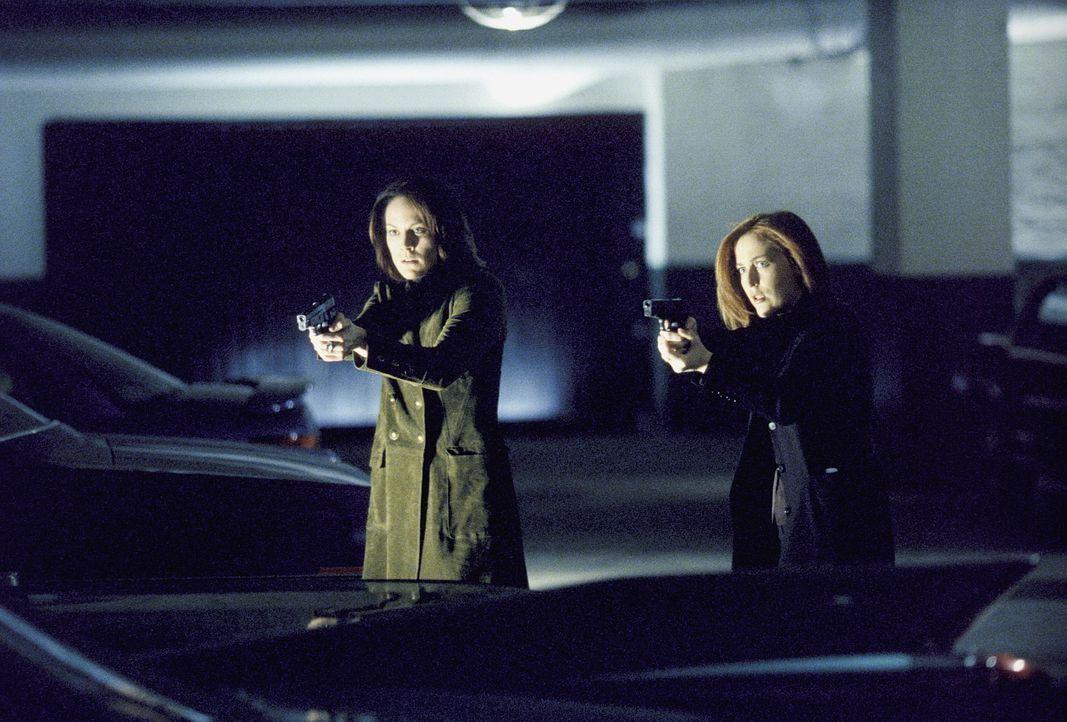Im Fahrstuhl entdecken Scully (Gillian Anderson, r.) und Monica (Annabeth Gish, l.) einen Mann, der den gesuchten Ring mit drei Sechsen trägt, und f... - Bildquelle: Twentieth Century Fox Film Corporation. All Rights Reserved.