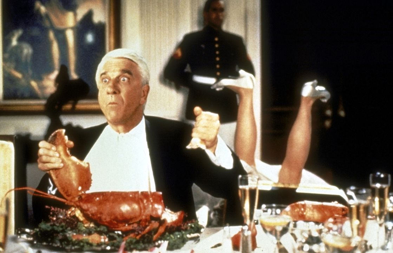 Als Belohnung für die Erschießung des 1000. Drogendealers erhält Lt. Frank Drebin (Leslie Nielsen, l.) eine Einladung zum Abendessen beim Präsidente... - Bildquelle: United International Pictures