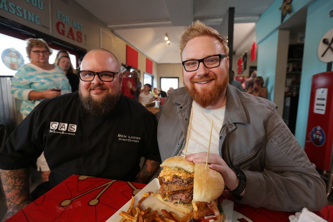 "Ben Loose (l.) von ""GAS Full Service Restaurant"" zeigt Josh Denny (r.) seinen berüchtigten Full Tank Burger ... - Bildquelle: 2017,Television Food Network, G.P. All Rights Reserved."