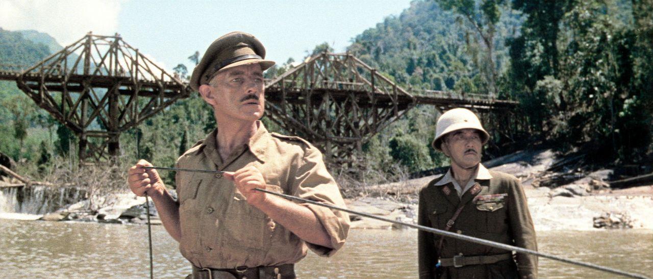 Bei ihrem täglichen Kontrollgang entdecken Oberst Nicholson (Alec Guinness, l.) und Oberst Saito (Sessue Hayakawa, r.) die Dynamitschnur und versuc...
