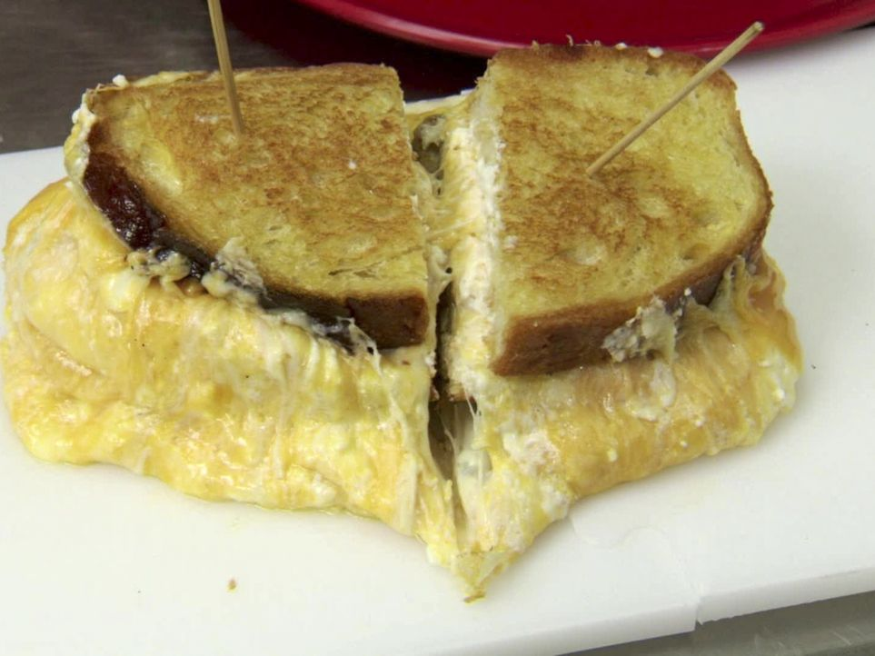 Im Melt Bar & Grilled in Lakewood, Ohio, tritt Adam Richman gegen ein gigantisches Grilled Cheese Sandwich an, das mit 14 Käsesorten gefüllt ist ... - Bildquelle: 2011, The Travel Channel, L.L.C. All Rights Reserved.