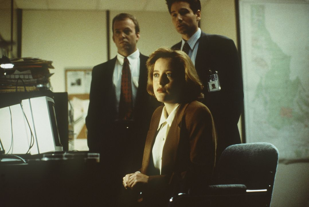 Die FBI-Agenten Scully (Gillian Anderson, M.) und Mulder (David Duchovny, r.) erfahren, dass ein geheimnisvoller Parasit fünf Männer getötet hat. - Bildquelle: TM +   2000 Twentieth Century Fox Film Corporation. All Rights Reserved.