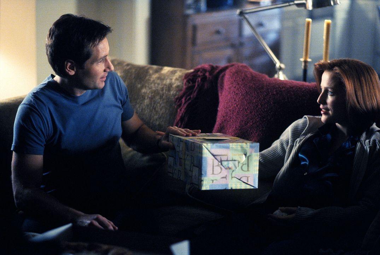 Mulder (David Duchovny, l.) besucht die hochschwangere Scully (Gillian Anderson, r.), um ihr ein Geschenk zu überreichen. - Bildquelle: TM +   2000 Twentieth Century Fox Film Corporation. All Rights Reserved.