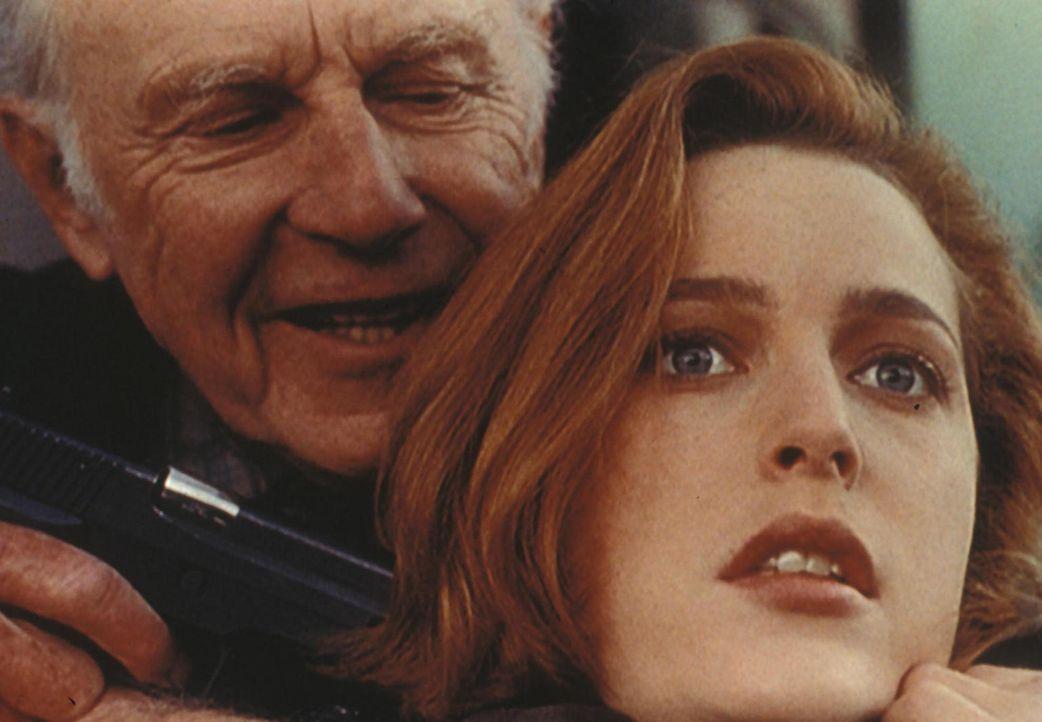 Scully (Gillian Anderson, r.) wird von dem russischen Agenten Vassily Peskow (Jan Rubes, l.) als Geisel benutzt, damit er fliehen kann. - Bildquelle: TM +   Twentieth Century Fox Film Corporation. All Rights Reserved.