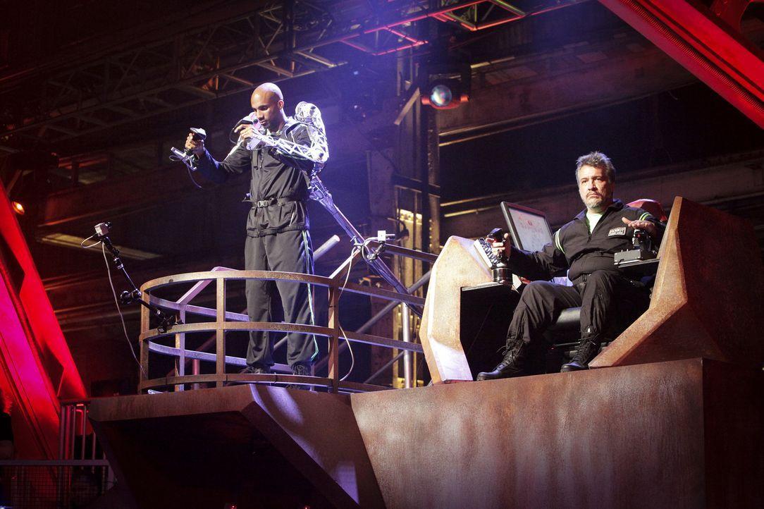 Team Brimstone gibt alles, um den gegnerischen Roboter zu besiegen: Robo-Jockey Devonric Johnson (l.) und sein Robo-Tech Russell Tait (r.) ... - Bildquelle: Nicole Wilder 2012 Syfy Media LLC