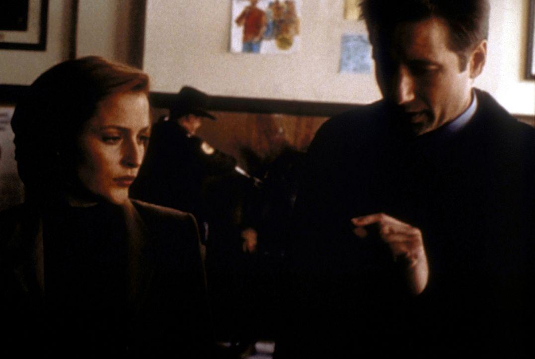Am Tatort entdecken Scully (Gillian Anderson, l.) und Mulder (David Duchovny, r.) etwas, das aussieht wie ein Stück geschmolzene Schuhsohle. - Bildquelle: TM +   2000 Twentieth Century Fox Film Corporation. All Rights Reserved.