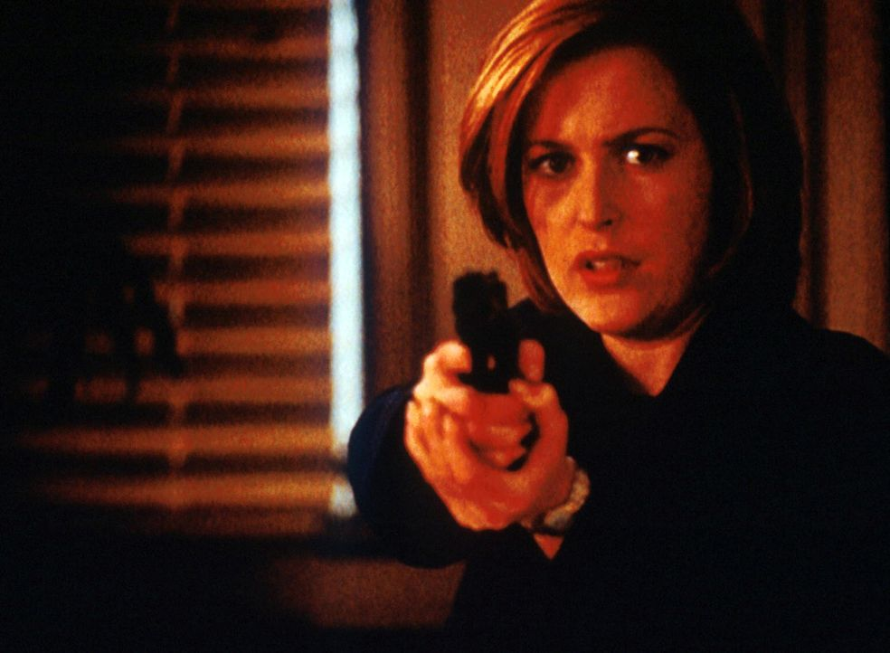 Scully (Gillian Anderson) hält den Bankräuber in Schach, der damit droht, sich selbst und alle Personen in der Bank in die Luft zu sprengen. - Bildquelle: TM +   2000 Twentieth Century Fox Film Corporation. All Rights Reserved.