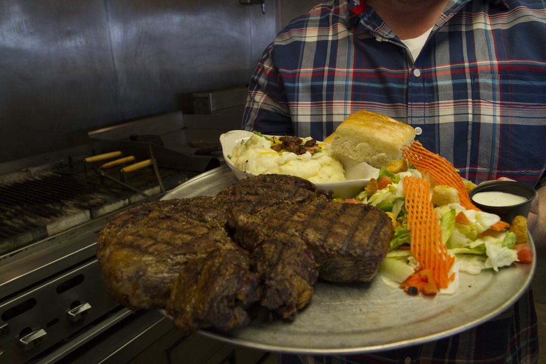"Im ""Bull Mountain Grille"" in Billings erwartet Casey Webb dieses Mal eine gigantische Steak-Challenge: ein 78-Unzen Rib Eye mit zwei Pfund Kartoffel... - Bildquelle: 2017,The Travel Channel, L.L.C. All Rights Reserved."