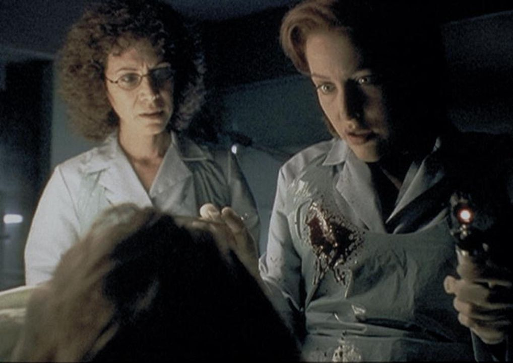 Scully (Gillian Anderson, r.) und die Gerichtsmedizinerin (Mindy Seeger, l.) stellen fest, dass die angebliche Geisel nicht durch eine Polizeikugel... - Bildquelle: TM +   2000 Twentieth Century Fox Film Corporation. All Rights Reserved.