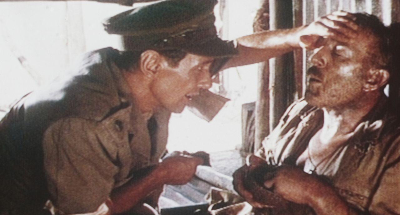 Oberst Nicholson (Alec Guinness, l.) ist am Ende seiner Kräfte angelangt. Major Clipton (James Donald, l.) kümmert sich um den Verletzten ...
